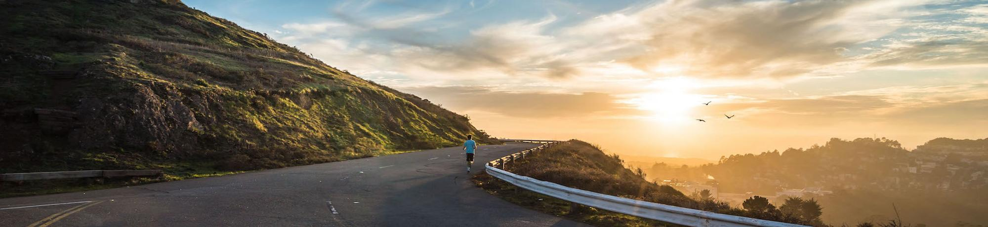 Man running in Californian hills at sunset looking at San Francisco in the distance